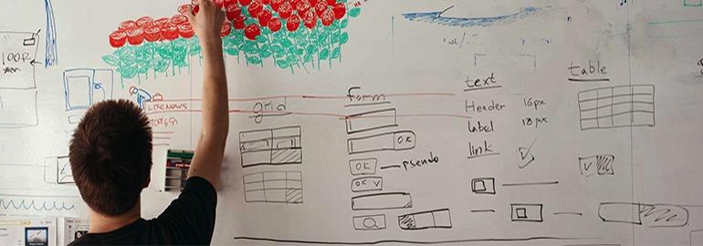 Молодой человек рисует маркерами цветы на доске с дизайн-схемами